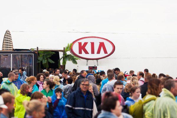 Het logo van KIA groot zichtbaar met publiek.