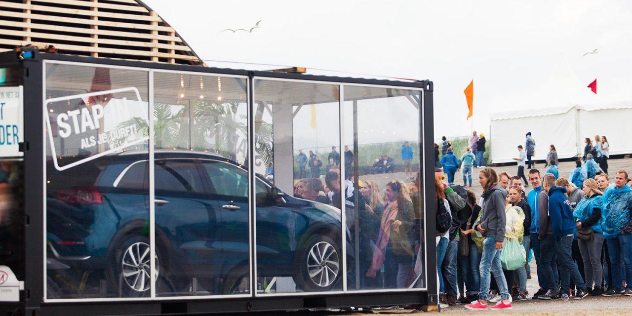 Een auto van Kia tentoongesteld in een glazen container, vast aan een romneyloods.